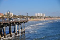 Santa Monica Pier looking towards Venice Beach in California. Busy day at the Santa Monica Pier overlooking Venice Beach. View of the water with people walking Royalty Free Stock Photos