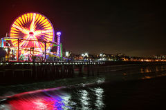 Santa Monica pier at night. The Santa Monica pier at night with the seascape in the background and reflection of the ferris wheel in the waves Royalty Free Stock Photo