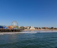Santa Monica Pier with the Pacific Park amusement center. And the Ferris wheel and the beach in the distance royalty free stock photos