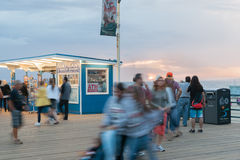 Santa Monica Pier people moving about at sunset Royalty Free Stock Image