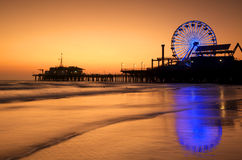 Santa Monica Pier reflections. Silhouette of Santa Monica Pier reflected in the wet sand of the beach stock photo