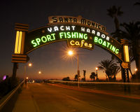 Santa Monica Pier at sunset. Entrance to Santa Monica Pier at dusk. The wording is lit up in neon royalty free stock photo