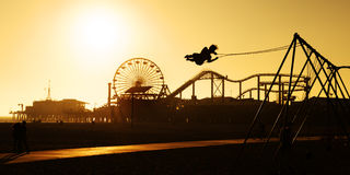 Santa Monica Pier at sunset. A man on a swing is silhouetted against the golden sky at Sunset on Santa Monica beach stock photography