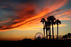Santa Monica Pier y palmeras en la puesta del sol Imágenes de archivo libres de regalías