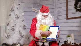 Santa montre le foyer avec un livre magique Photographie stock libre de droits