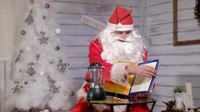 Santa montre le foyer avec un livre magique Photos stock