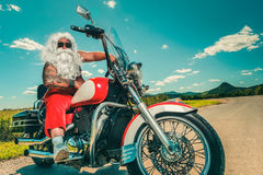Santa on a motorcycle. Sunburned Santa biker riding motorcycle on summer vacations Royalty Free Stock Images