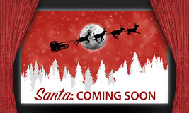 Santa on movie theater screen. Text graphics Santa coming soon with silhouette of sleigh and reindeer flying in skies on movie theater screen behind red velvet Stock Images