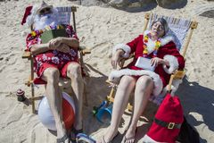 Santa and Mrs Claus sleeping with books on beach. Santa Claus in red swimming trunks and Hawaiian shirt lounging on sandy beach with Mrs Claus sleeping on sandy stock photos