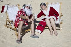 Santa and Mrs Claus taking selfie on beach. Santa Claus in red swimming trunks and Hawaiian shirt lounging on sandy beach with Mrs Claus taking selfie stock photos