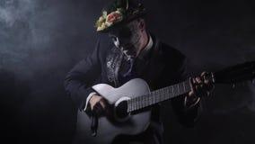 Santa Muerte Carnaval, een mens in zwart kostuum speelt een zwart-witte gitaar stock footage