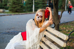 Santa Muerte. The girl in the image of Santa Muerte is sitting on a bench Stock Image