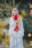 Santa Muerte. The girl in the image of Santa Muerte stands with flower in hands Royalty Free Stock Image