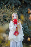 Santa Muerte. The girl in the image of Santa Muerte stands with flower in hands Royalty Free Stock Photography