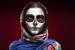 Santa muerte makeup. Young woman with santa muerte makeup on red background Stock Photo