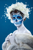 Santa Muerte woman at blue background. Santa Muerte concept of make up. Young woman with short curly hair and creative visage. White flowers in hair, make up Stock Photos