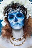 Santa Muerte woman at blue background. Santa Muerte make up. Young woman with short curly hair and creative visage. White flowers in hair, make up, portrait at Stock Photo