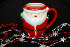 Santa mug with hot drink and shiny string beads in front of it. Black background Stock Photography