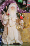 Santa near chrismas tree with gift. Golden santa near decorative chrismas tree with gift Stock Images