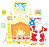 Santa near a fireplace. Vector illustration of Father Christmas with his gift bag standing near a chimney with stockings for presents Royalty Free Stock Image