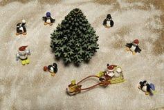 Santa no trenó com rena corre em torno da árvore de Natal verde e dos muitos pinguins e do homem da neve foto de stock royalty free