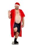 Santa obesa divertendosi sulle scale Fotografia Stock