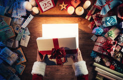 Santa opening a gift box. Santa Claus opening a magic bright Christmas gift box, presents and letters all around, hands top view Royalty Free Stock Image