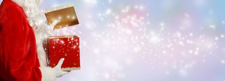 Santa opening a gift box. On a shiny light background royalty free stock images