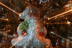 Abstract Santa Ornament on Christmas Tree with Light Rays Close. A Santa Ornament hangs on a Christmas tree with motion blur used to make tree lights look like Stock Images