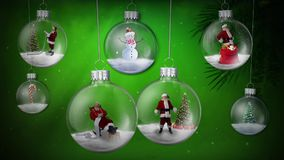 Santa Ornaments Swinging on Green Background. This video Features glass ornaments filled with live Santas swinging against a green atmospheric particle stock footage