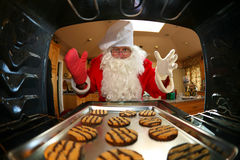 Santa at oven. Santa in kitchen whipping up a batch of cookies, then eating some of them with a glass of milk Royalty Free Stock Photography