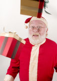 Santa with Packages In The Air. Shots of a REAL Santa in the studio Stock Image