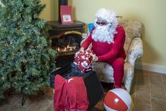 Santa packing suitcase for a beach holiday after Christmas royalty free stock photo