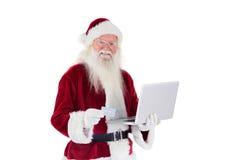 Santa paga com cartão de crédito em um portátil Fotos de Stock