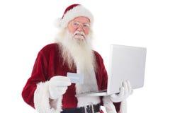 Santa paga com cartão de crédito em um portátil Foto de Stock