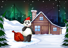 A Santa panda with a red sack full of gifts Stock Photos