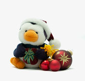 Santa Penguin with present and baubles. Cuddly penguin wearing a santa hat and holding a present with red christmas baubles beside Stock Photos