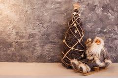 Santa pequena que senta-se em um trenó perto da árvore de Natal de vime Fotos de Stock