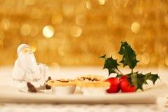 Santa pica las empanadas y acebo Fotos de archivo libres de regalías