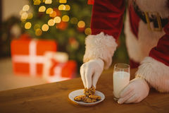 Santa picking cookie and glass of milk Stock Images