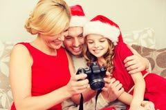 Οικογένεια στα καπέλα αρωγών santa που εξετάζει τα pictires Στοκ Εικόνες