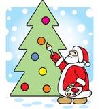 Santa pinta un árbol de navidad. Foto de archivo