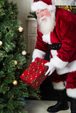 Santa places gift under tree Royalty Free Stock Image