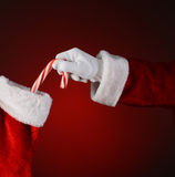 Santa Placing Candy Cane Into Stocking Stock Image