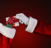 Santa Placing Small Gift Into Stocking Royalty Free Stock Images