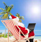 Santa playing with laptop on a beach Royalty Free Stock Image
