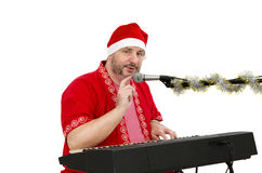 Santa plays in electric piano. Man in Santa suit plays in electric piano on a white background Royalty Free Stock Photography