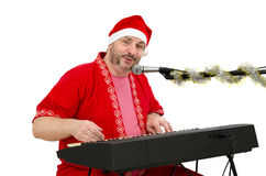 Santa plays and sings on electric piano Royalty Free Stock Photography