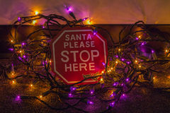 Santa Please Stop Here Sign and Christmas Lights Stock Images