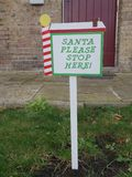 Santa please stop here sign. Planted in the grass outside the front door royalty free stock photo